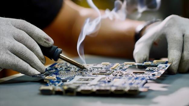 Repairman in gloves is soldering motherboard of computer device in workshop