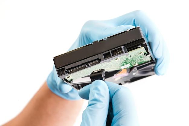 파란색 runnber 장갑에 수리 공 손을 녹색 칩으로 컴퓨터 하드 드라이브 디스크를 보유하고 있습니다.