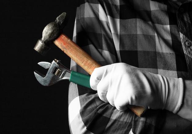 장갑에 수리 공 손을 검정 배경 위에 망치와 렌치 도구로 닫습니다.