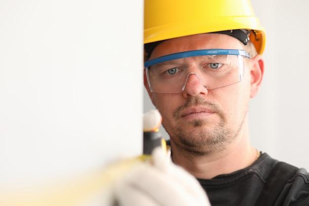 Repairman in helmet and mask, measures tape measure