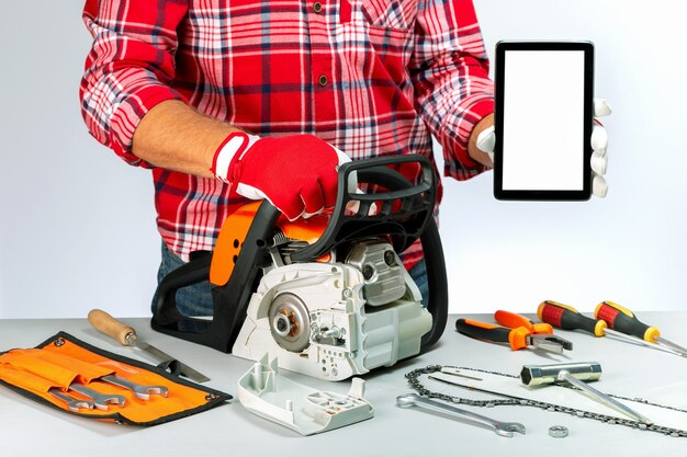 Repairman holding digital tablet and chainsaw