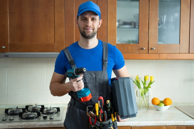 Repairman holds a screwdriver and a suitcase of tools in the kitchen and looks at the camera