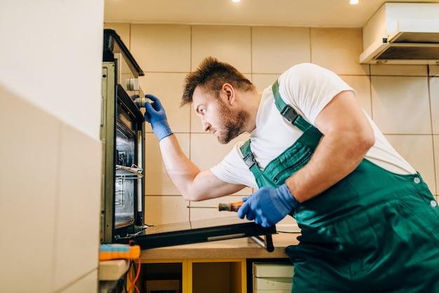 Ремонтник в форме проверяет печь, техник. профессиональный работник делает ремонт по дому, услуги по ремонту дома