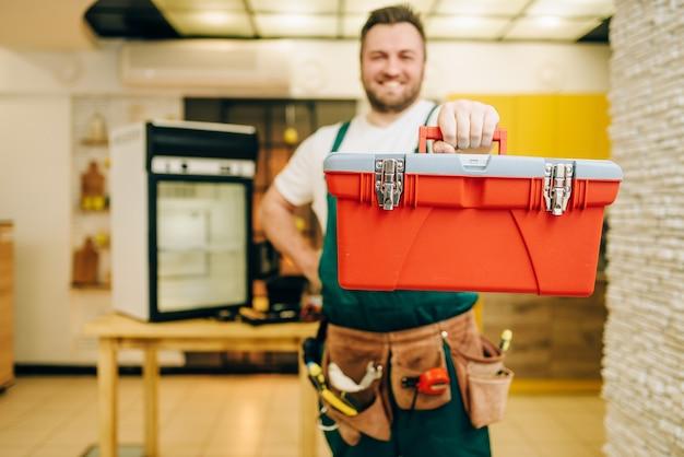 Ремонтник в униформе держит ящик для инструментов