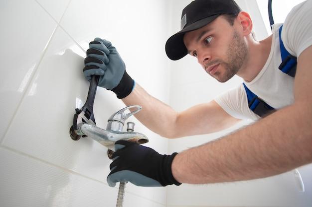 制服を着た修理工が特別な道具を使って古い浴室の蛇口を修理しています