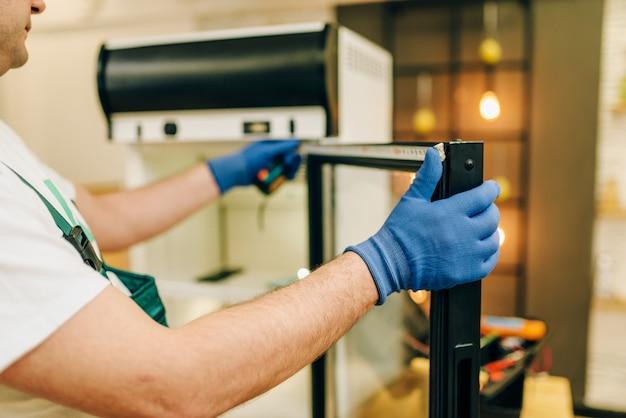 Ремонтник в униформе ремонтирует холодильник дома.