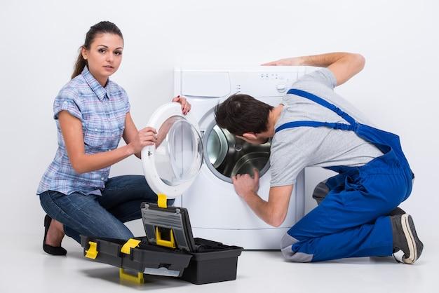 Repairman is repairing a washing machine for housewife.