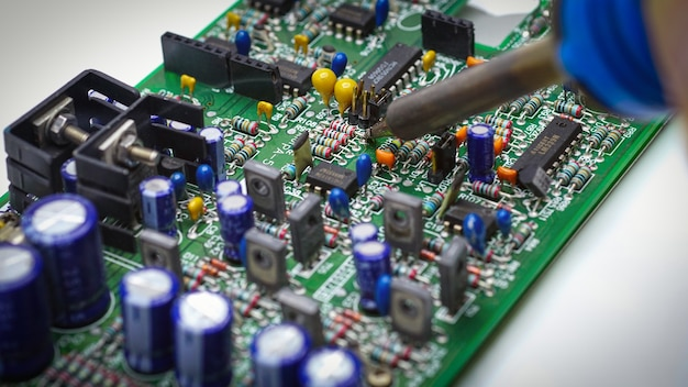 Repairman is soldering circuit board of electronic device