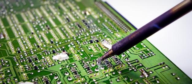 수리공은 전자 장치의 회로 기판을 납땜하고 있습니다