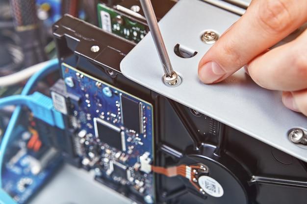 Ремонтник откручивает винт жесткого диска разобранного системного блока компьютера, крупным планом.