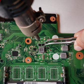 수리공이 핀셋과 열풍 송풍기를 사용하여 마더보드를 수리하고 있습니다.