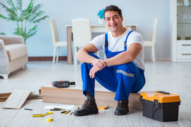 Repairman laying laminate flooring at home