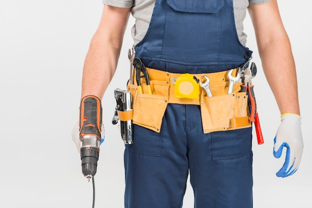 Repairman in overall holding drill