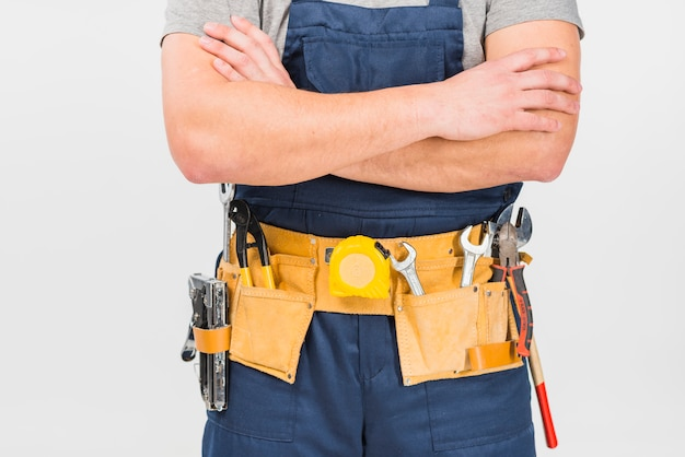 Repairman in overall standing with crossed arms