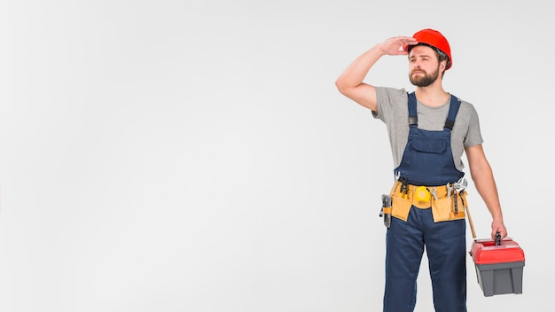 Repairman in overall with tool box looking away