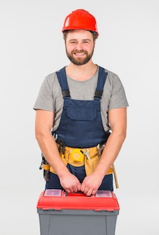 Repairman in overall with tool box smiling