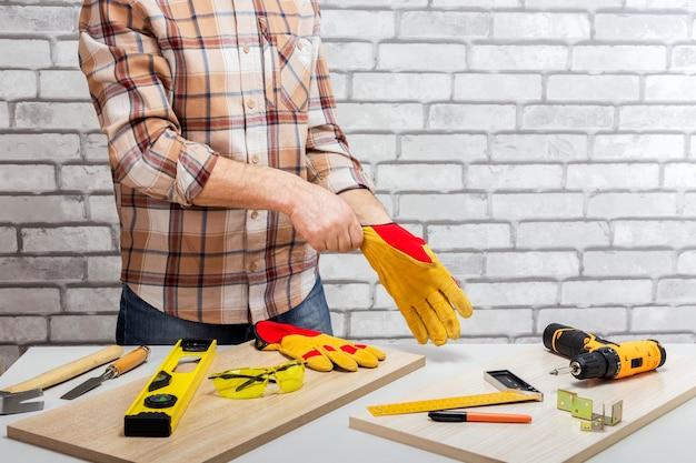 Ремонтник надевает защитную перчатку для работы с инструментами на столе и стене из белого кирпича