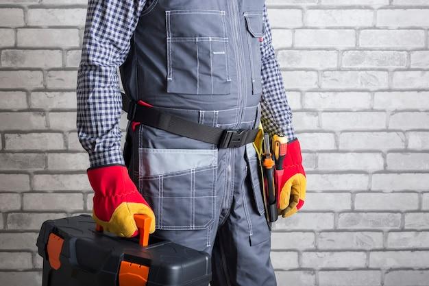수리공 작업 준비. 벽돌 벽 표면에 도구 상자와 서비스 남자.