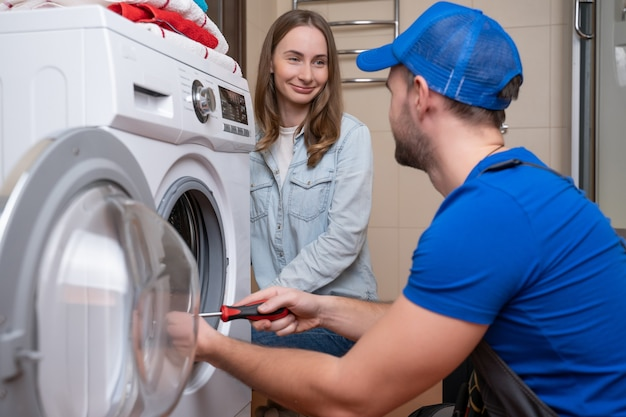 Repairman repairs a washing machine in front of a woman a man communicates with the owner of a washing machine