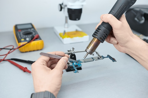 Repairman soldering components in motherboard while fixing damaged smart phone, using tweezers and iron