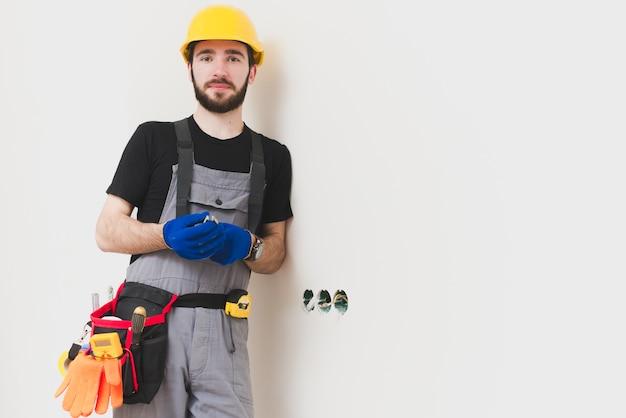 Ремонтник, стоящий у отверстий в стене