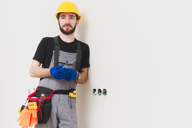 Repairman standing at holes in wall