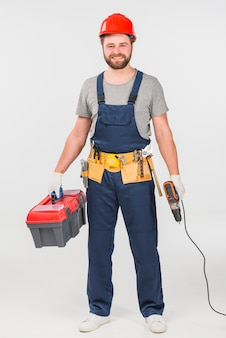 Repairman standing with tool box and drill