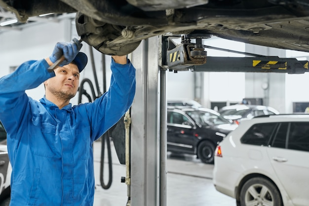 Repairman trying to remove outdated detail from car chassis
