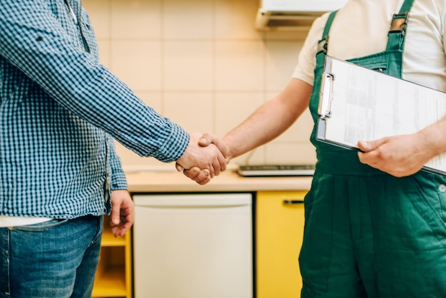 Repairman in uniform and customer shake hands, handyman.