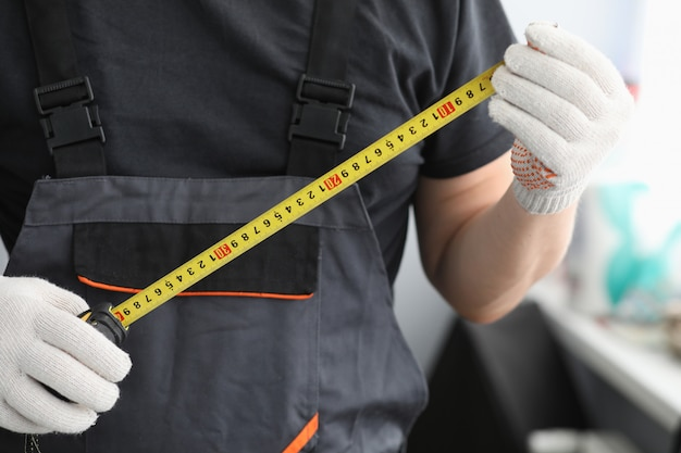 Repairman in uniform gloves measures tape measure