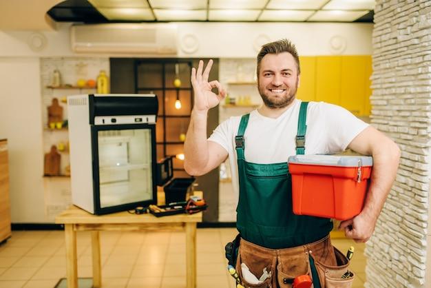 Repairman in uniform holds toolbox