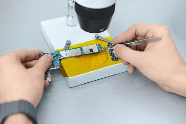 Ремонтник с помощью пинцета удерживает электронные компоненты печатной платы во время ремонта мобильного телефона под микроскопом