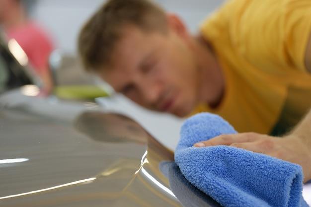 マイクロファイバークロスのクローズアップで車のボンネットを拭く修理工