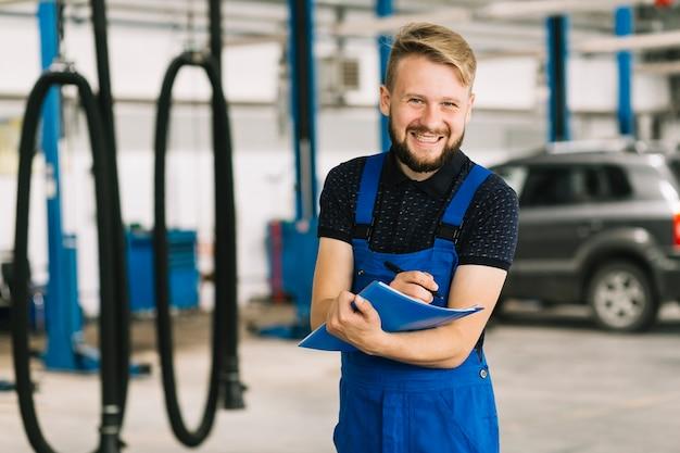Repairman with folder smiling at workshop