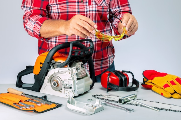 Repairman with industrial protective wear and tools. serviceman is repairing a chainsaw in repair shop.
