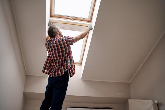 天窓の横に巻尺を持った修理工
