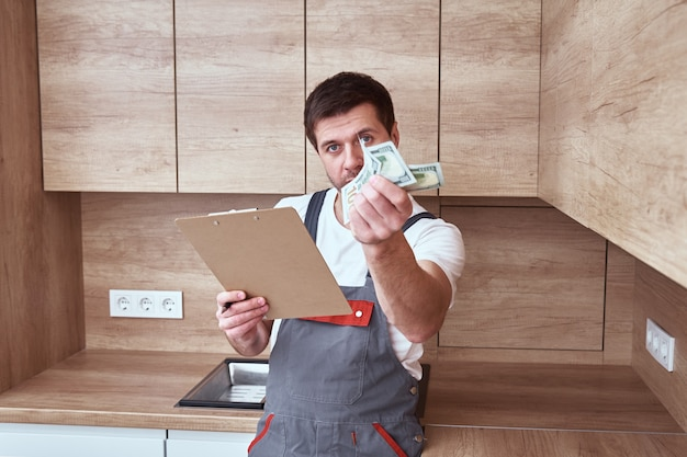 Repairman with payment and agreement contract in the kitchen