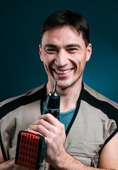青にカメラにポーズをとって電気ドリルを保持している修理労働者。構築ツールのコンセプト