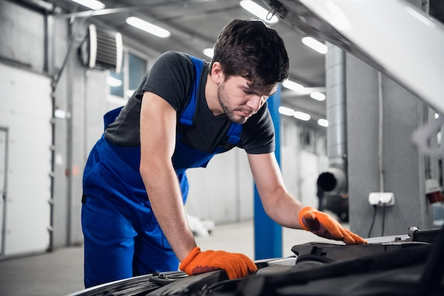 Repairman in working gloves opened the hood of the car and checks the engine
