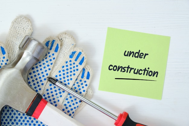 Repairman working tools with a sticker and an inscription on it under construction on a white wooden background
