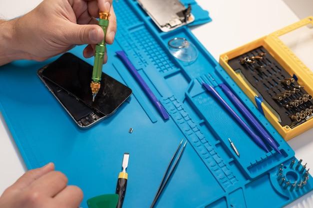 スマートフォンを修理する修理工の職場技術者