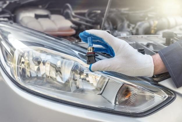 ヘッドランプの欺瞞の下で新しい車の電球を保持している修理工