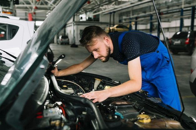 Repairmen inspecting car motor