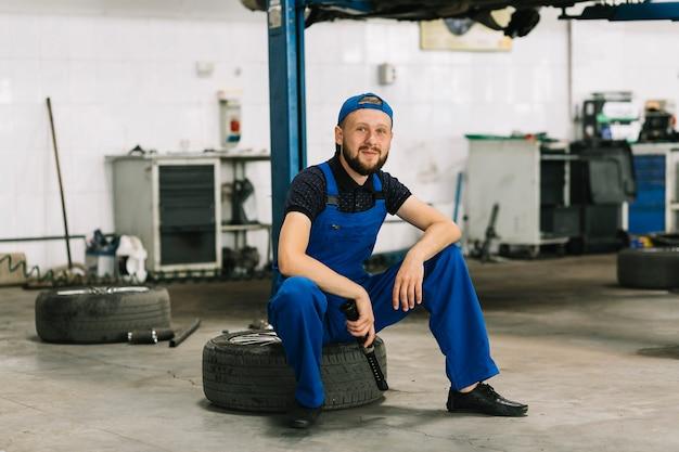 Repairmen sitting on tire at garage