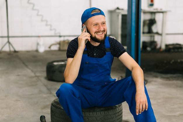 Repairmen talking on phone at workshop