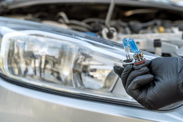 Ремонт, держащий новую автомобильную лампочку под обманом для фары, автомобиля в качестве фона. крупный план
