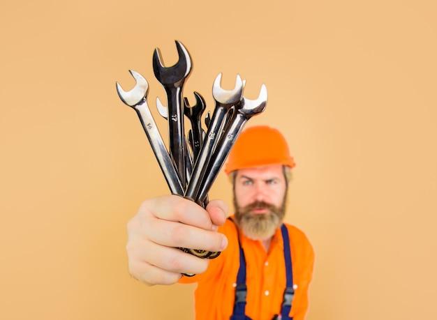修理ツールの労働者は、レンチビジネス建築業界の技術スパナひげを生やしたビルダーを保持します