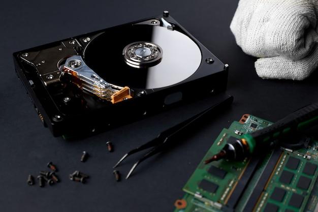 엔지니어가 깨진 컴퓨터 하드 디스크 드라이브를 수리합니다.