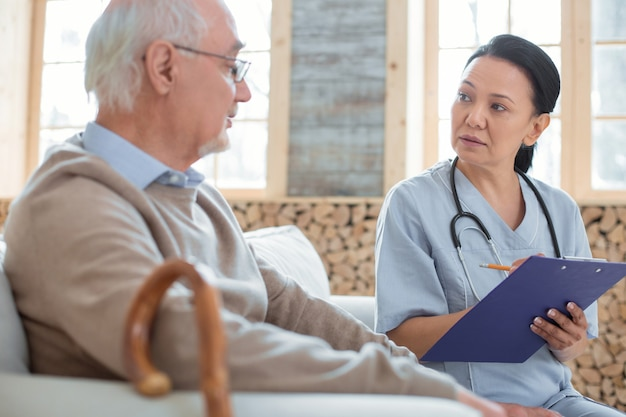 Repeat please. upset concentrated doctor holding clipboard while taking notes and communicating with senior man