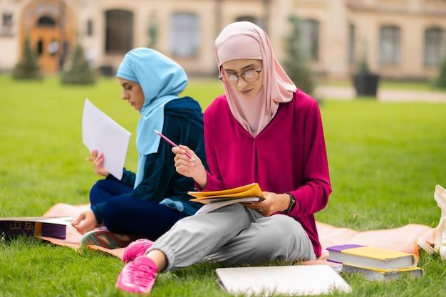 繰り返し素材。草の上に座って一緒に資料を繰り返す2人のイスラム教徒の留学生